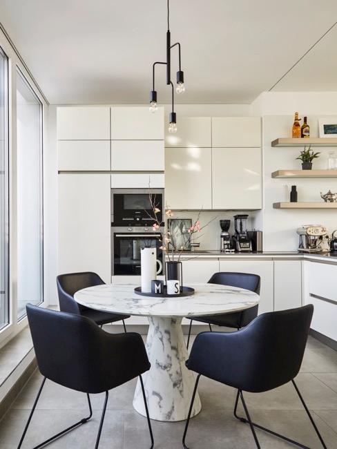 cucina bianca con tavolo rotondo in marmo e sedie blu