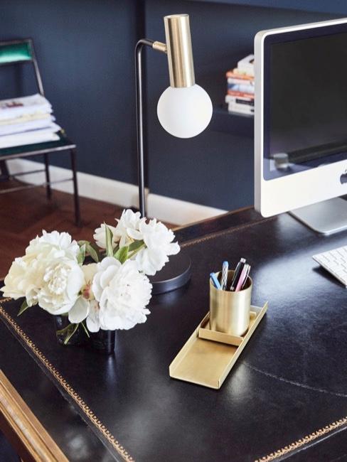 oficina en casa con un escritorio oscuro, lámpara de mesa, flores blancos y ordenador