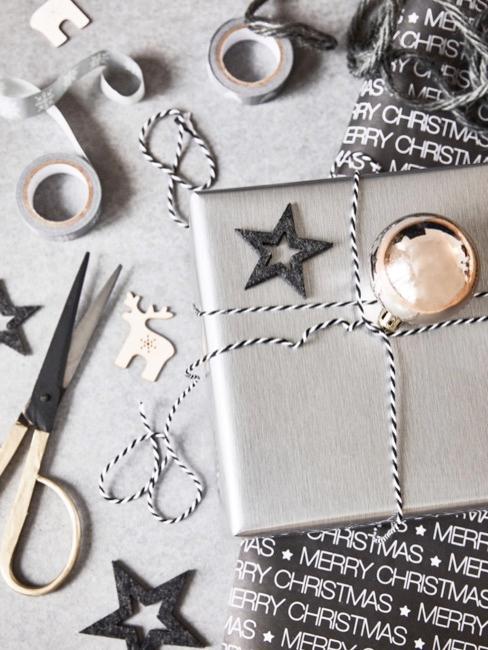 NahaufClose-up tafel met zilveren geschenk, schaar en decoratief materiaalnahme Tisch mit silber Geschenk, Schere und Dekomaterial