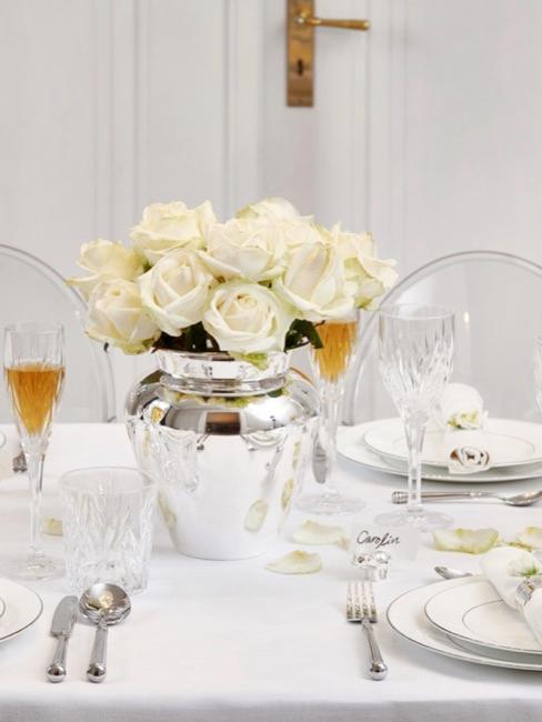 Bloemen voor de bruiloftstafel met witte rozen en een feestelijk gedekte tafel in het wit