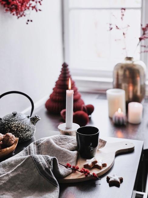 Tavola con tagliere in legno, teiera, candela accesa e decorazioni natalizie