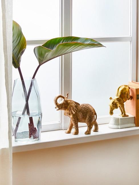 Fenster mit Fensterbrett auf dem Bücher, eine Vase mit Blättern und eine Elefantenfigur dekorativ aufgestellt sind