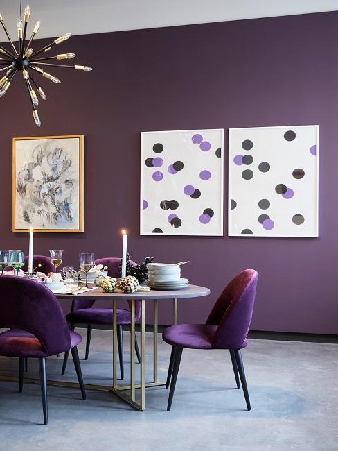 Esszimmer im Maximalismus mit Polsterstühlen einem großen gedeckten Esstisch und einer lila Wand.