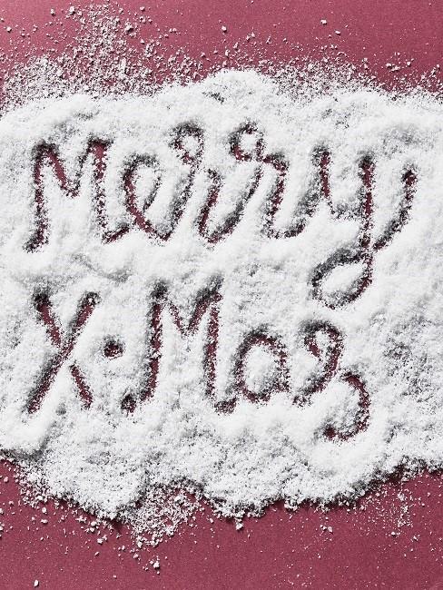 Merry X-Mas in Schnee geschrieben auf rotem Tisch
