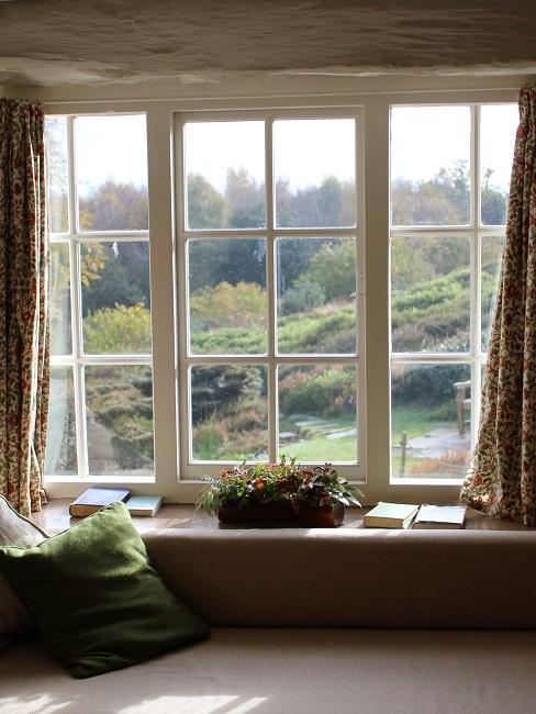 Erker mit einem großen Fenster und einer Fensterbank zum Sitzen davor mit Bücherstapeln.