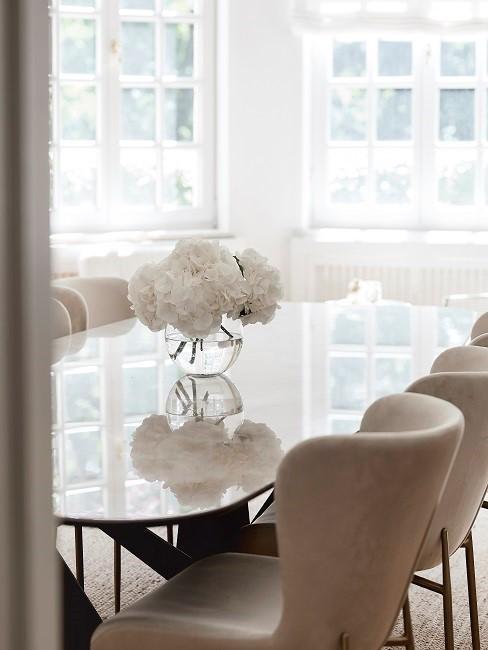 Ovaler Esstisch aus Glas mit rosa Stühlen und Pflanzendeko