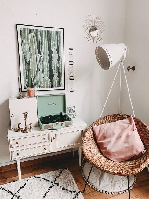 Vintage Schlafzimmer mit weißer Retroleuchte, Kommode , Sessel und rosa Kissen