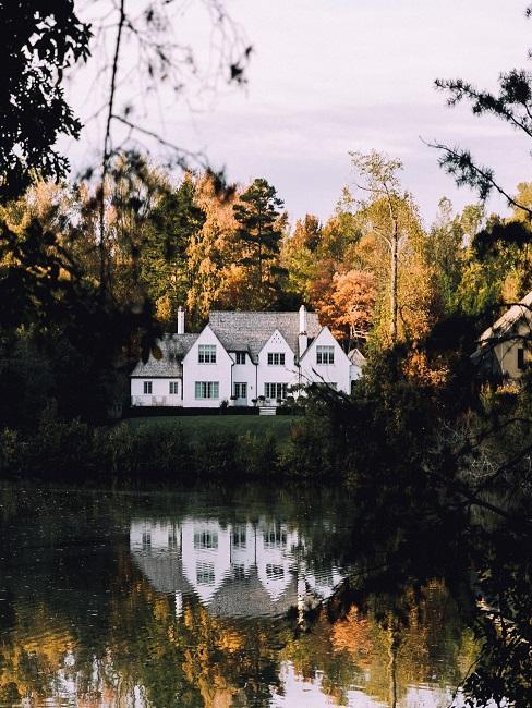 Ein großes Haus an einem See von Wäldern umgeben.