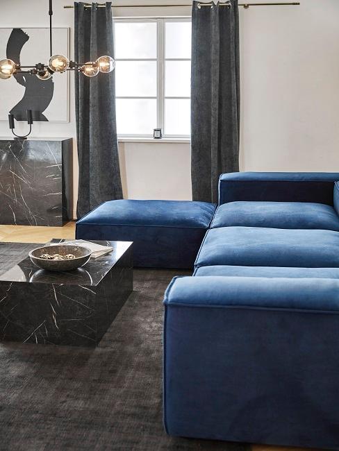 Wohnzimmer mit blauer Textil-Couch zu schwarzen Marmor-Pieces und einer modernen Lampe aus Metall