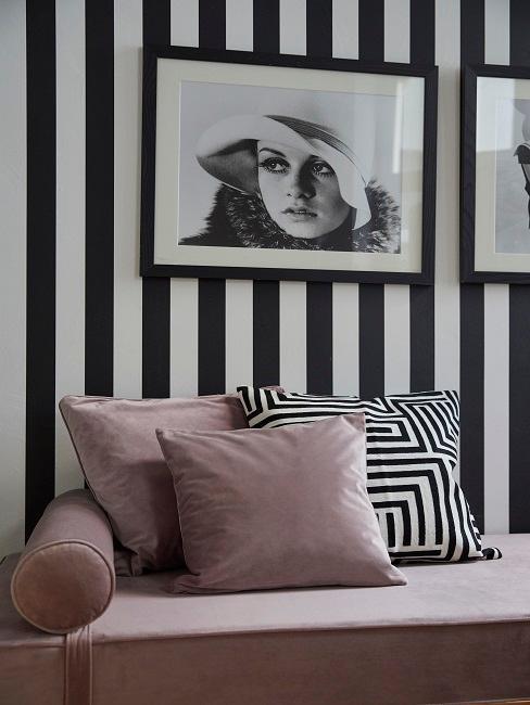 Eine schwarz-weiße Tapete mit Retro Schwarz-Weiß Wandbildern und einer Couch in Rosa mit passenden Dekokissen