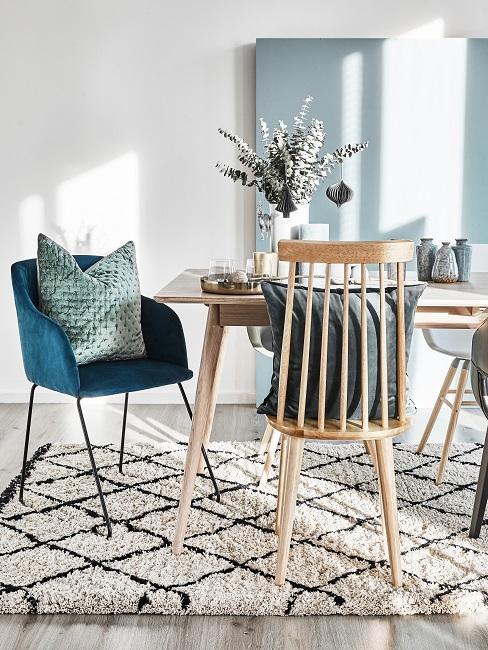 Gedeckte Farben Esszimmer mit blaugrünen Sessel, grünen Kissen, Holzmöbeln und kariertem Teppich
