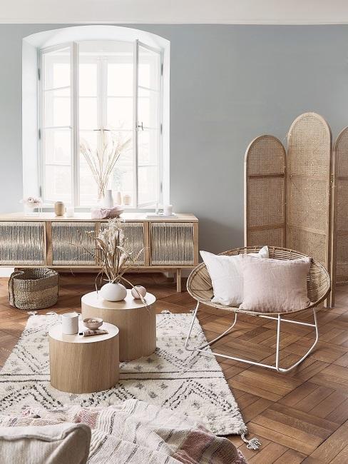 Gedeckte Farben Möbel aus Holz und Rattan mit weißen und rosa Kissen und grafischem Teppich