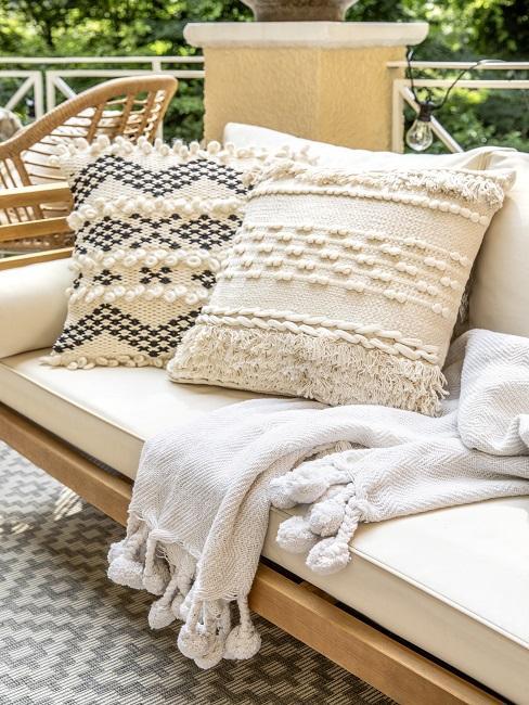Balkon mit einer Sitzbank, Zwei Ethno-Boho-Kissen als günstige Deko