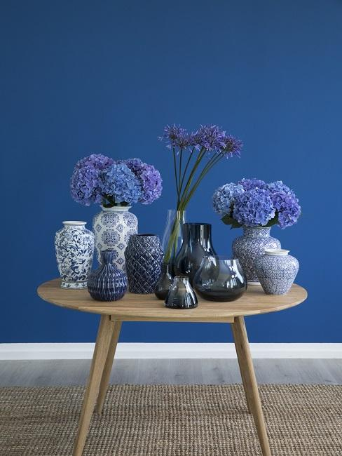 Classic Blue Pantone Trendfarbe Wand mit Holztisch und Vasen und Blumen