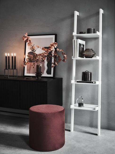 Designer Flur mit grauer Wand, schwarzem Sideboard, Dekoleiter und rotem Hocker