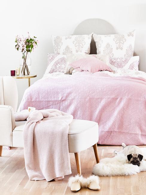 Dormitorio en colores rosas con carlino tumbado sobre la alfombra