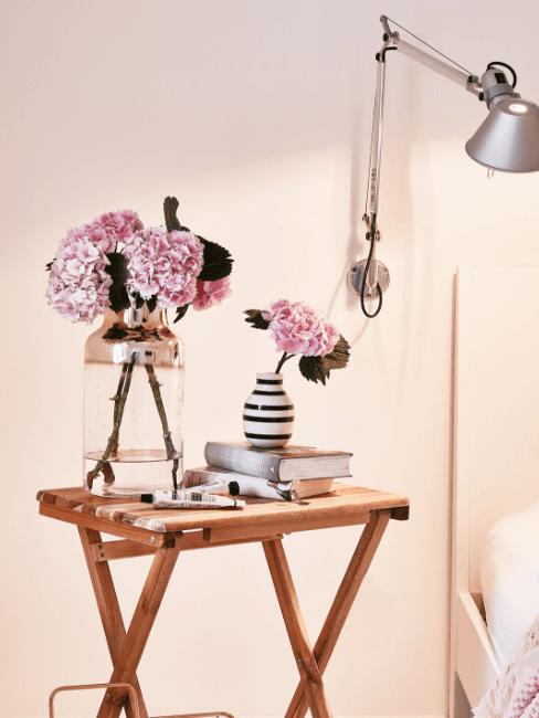 Vasi di vetro con fiori su tavolino in legno