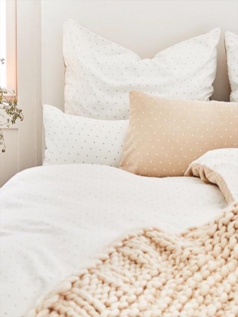 Lenzuola bianche con cuscini e plaid in lana giallo tenue