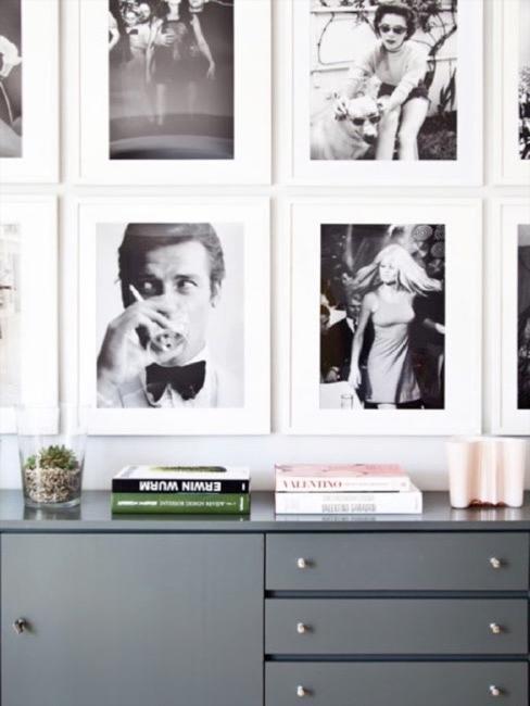 Cómoda gris con libros y plantas suculentas con pared de cuadros en blanco y negro