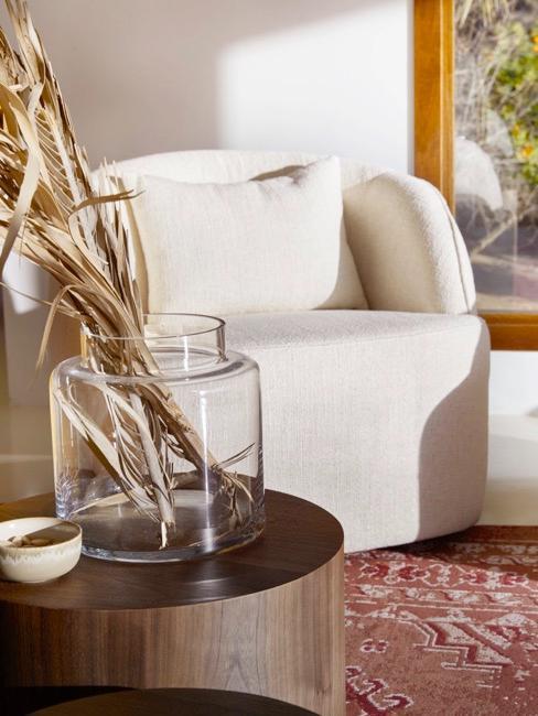 Dettaglio di salotto boho con poltroncina bianca e tavolino in legno