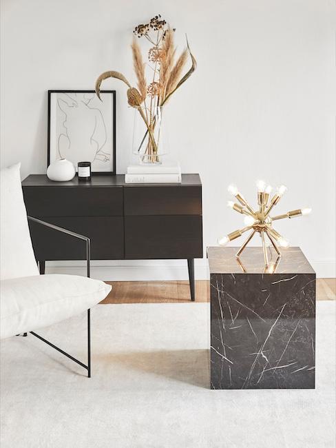 Sala de estar en tonos blaco, negro y dorado con mesilla de mármol