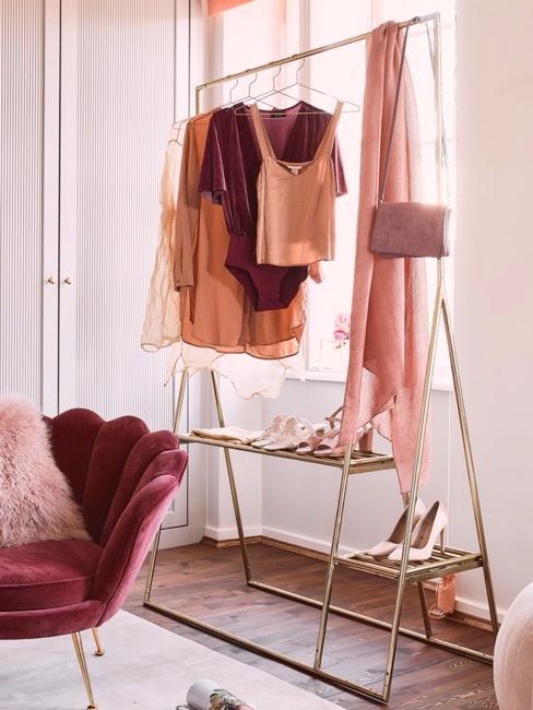 Porte-manteau doré avec des vêtements rose clair ou crème devant un fauteuil rouge bordeaux
