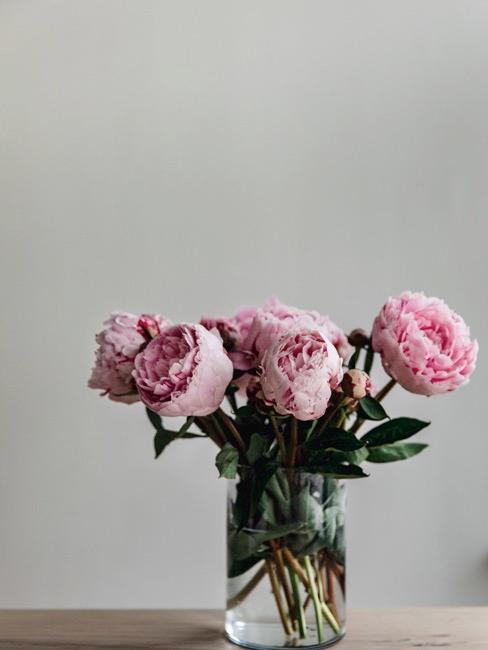 Pivoines roses en vase en verre sur table