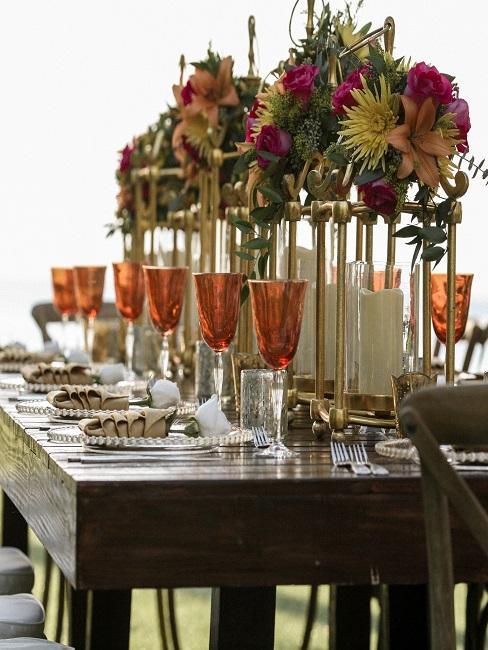 Großer gedeckter Holztisch, in der Mitte ein goldfarbenes Gestell, das mit bunten Blumen dekoriert ist