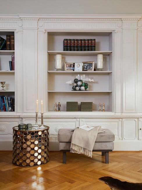 Wohnzimmer von Tamara Gräfin von Nayhauß mit Einbauregalen mit Schnörkeleien, davor ein moderner Beistelltisch aus goldfarbenem Metall neben einer Velours-Sitzbank