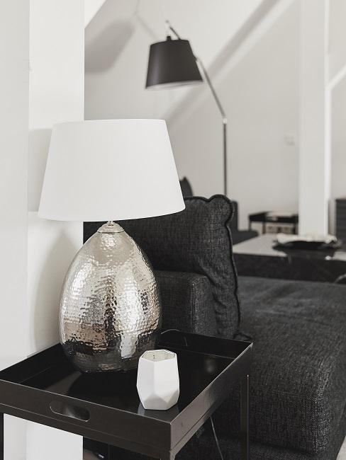 Ei Beistelltisch mit dekorativer Tischlamoe neben der Sofaecke in einer Männerwohnung