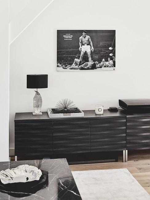 Ein schwarzes Sideboard im Wohnzimmer der Männerwohnung mit cleaner Deko auf der Ablage und einem Schwarz-Weiß-Wandbild darüber