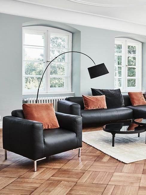 Ein schwarzes Ledersofa und passender Sessel mit Dekokissen, dahinter eine Stehleuchte in Schwarz