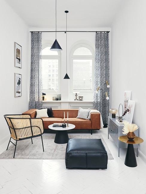 Bauhausstil Wohnzimmer mit brauner Ledercouch, schwarzem Lederpouf, Hängeleuchten und Teppich