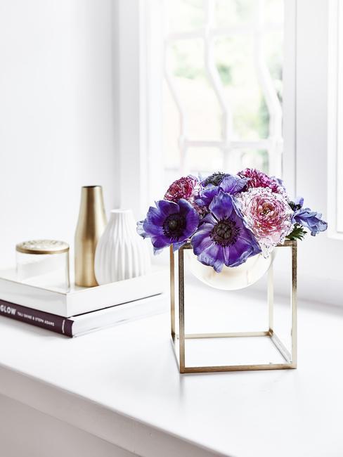 Jarrón con flores en morado lila sobre fondo blanco