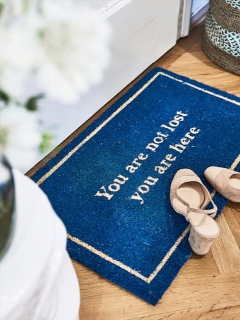 Paillasson en bleu cobalt avec lettrage, posé à l'entrée, paire de chaussures femme posée dessus