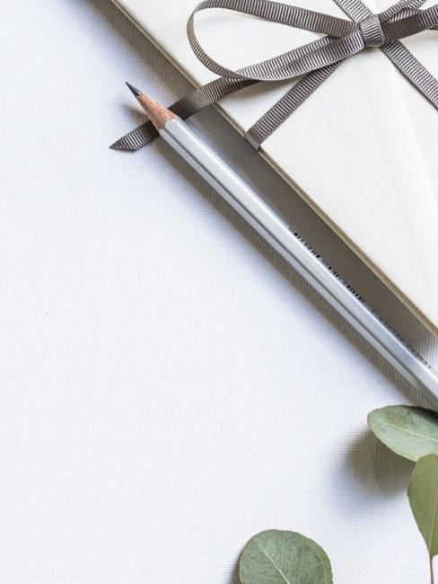 Enveloppe beige avec ruban gris, crayon pointu et feuilles d'eucalyptus sur fond clair