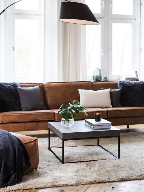 Chambre meublée d'un canapé en cuir brun, d'une table basse et d'un lampadaire arc