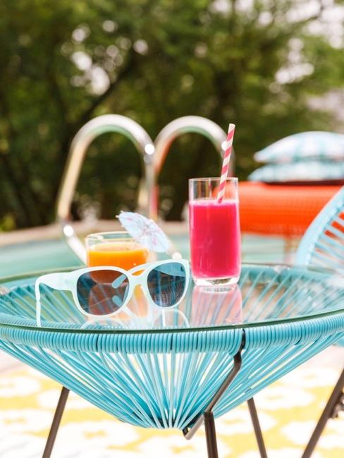 Table d'appoint acapulco bleu avec cocktail rose et lunettes de soleil
