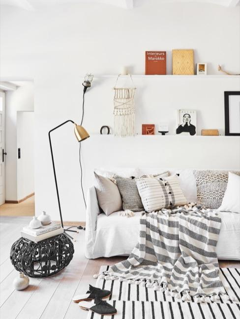 Salon blanc avec étagères murales, canapé crème et tapis monochrome
