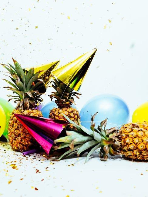 Ananas et décoration pour fête sur fond blanc et confettis