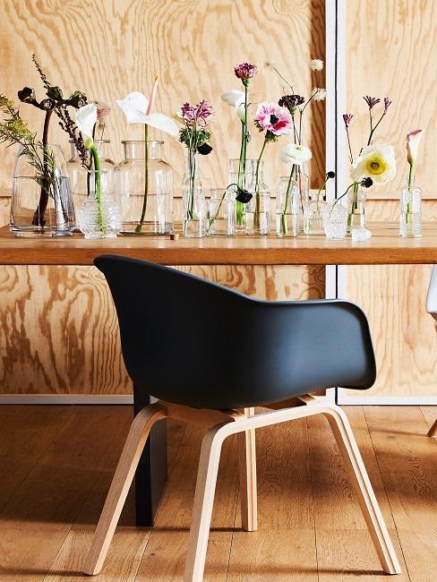 Schwarzer Stuhl vor Holztisch mit Vasen mit einzelnen Blumen