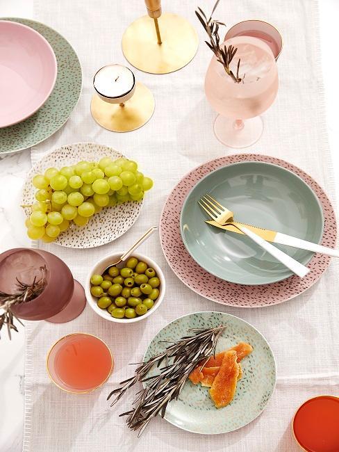 Bunt gedeckter Tisch mit Trauben und Oliven