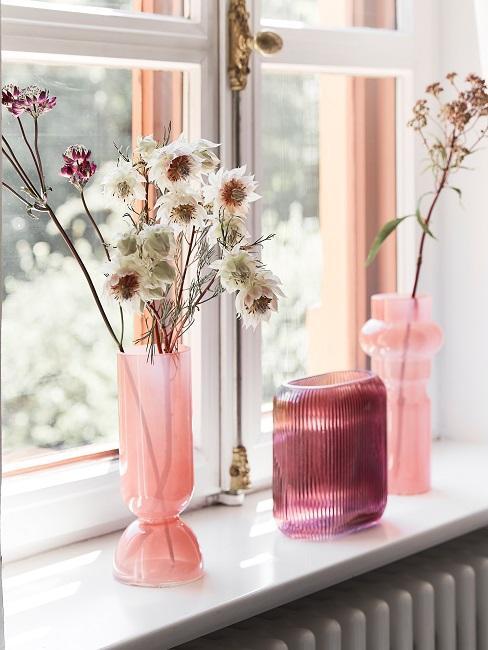 Fensterbank mit rosafarbenen Vasen
