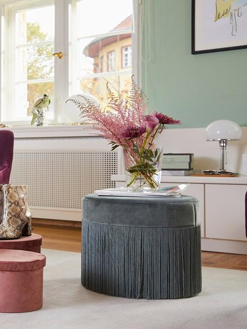 Rosa Blumen auf grauem Pouf im Wohnzimmer