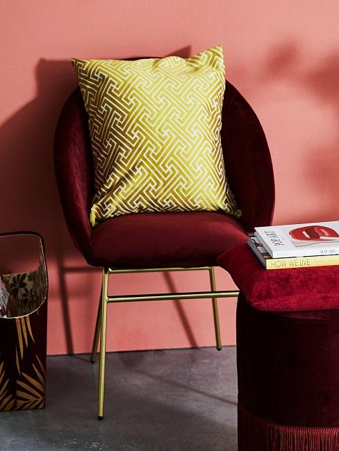 Gelbes Kissen auf rotem Stuhl neben Pouf