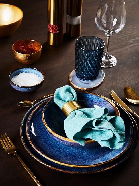 Blaues Tischgedeck mit Goldelementen auf dunklem Tisch
