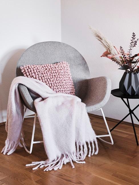 Grauer Sessel mit rosa Deko neben Beistelltisch