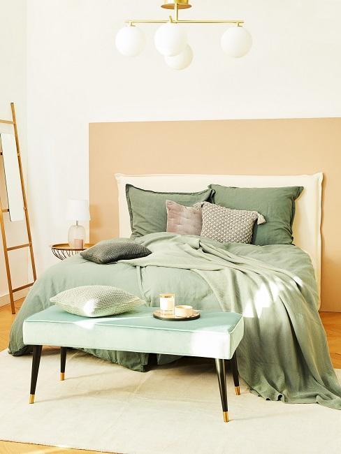 Bett mit pastellgrüner Bettwäsche mit Bank