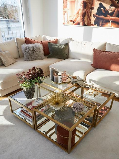 Helles Wohnzimmer mit weißer Couch und goldenen Couchtischen