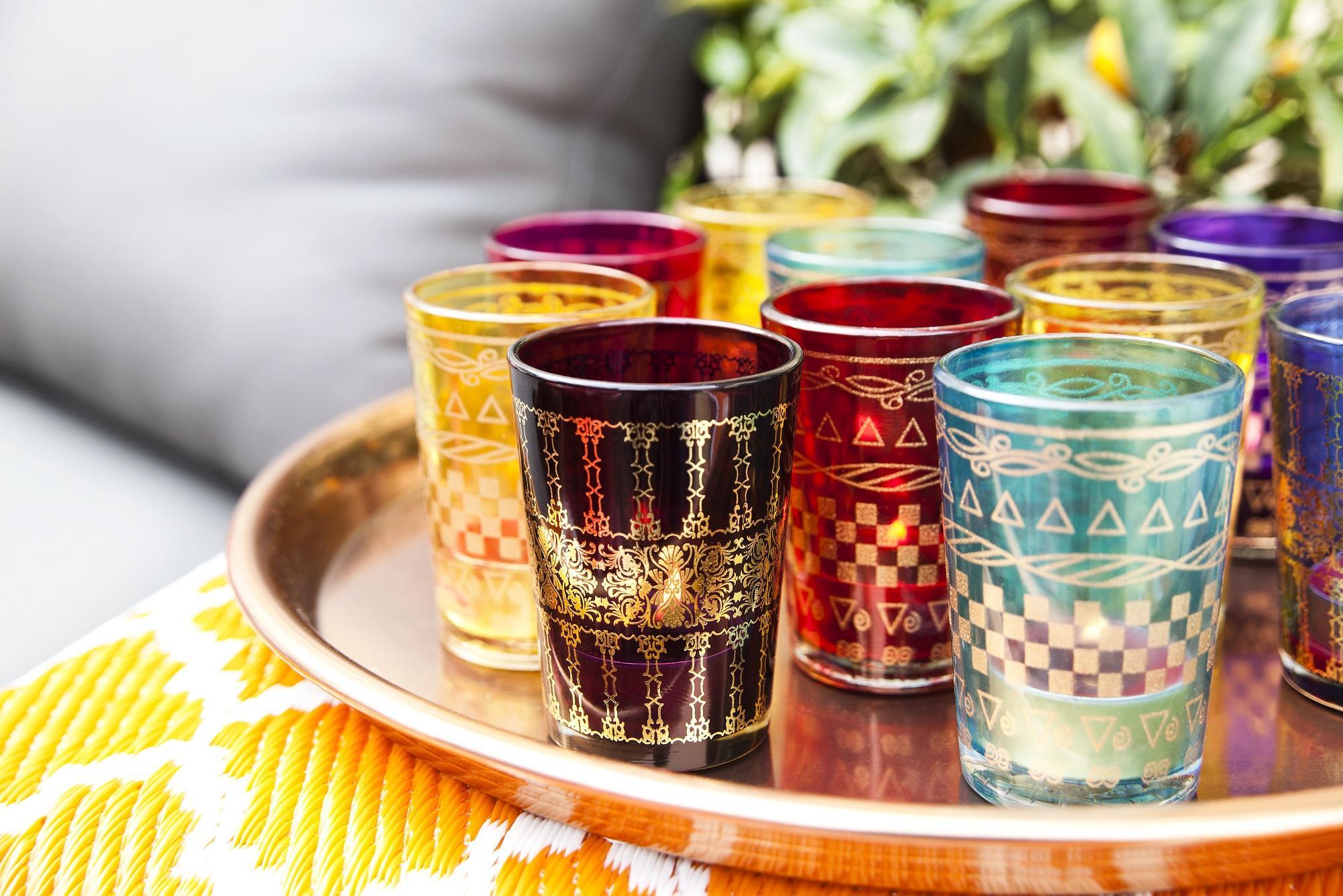 Disponete il vassoio ripieno di candele profumate, anch'esse con vasetti in vetro multicolor, come centrotavola.